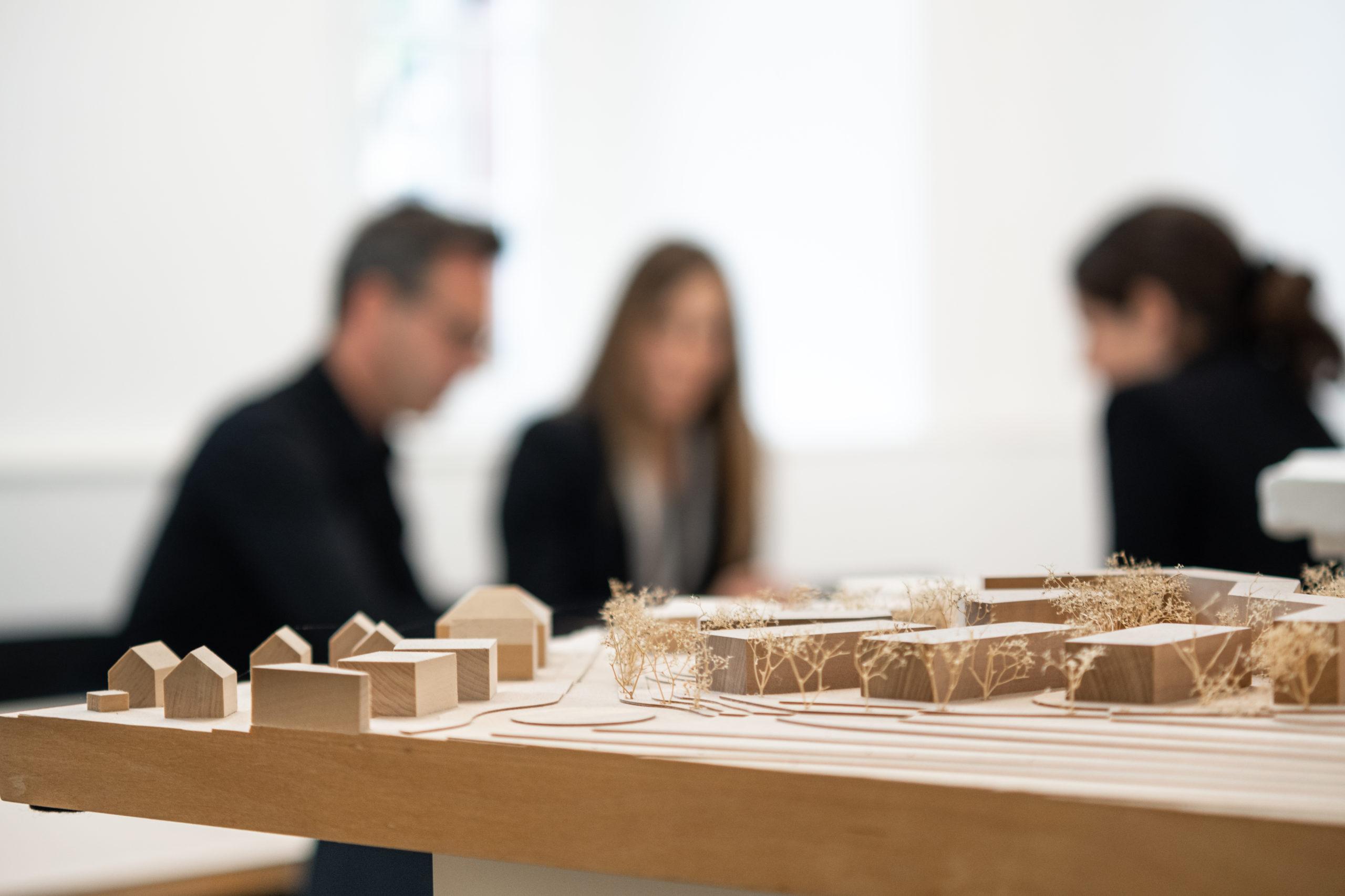 cfw architekten personen unscharf hinter eine Architur Modell im Buero01 scaled